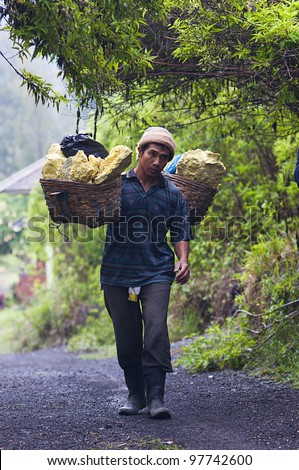 IJEN VOLCANO, INDONESIA - DEC 16: Worker carries sulfur inside Ijen crater on December 16, 2011 in Ijen Volcano, Indonesia. He carries the load of around 60kg to the top of the rip and then 3km down. - stock photo