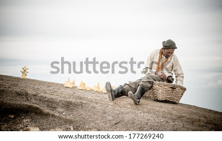 IJEN VOLCANO, INDONESIA - FEB 15:Man selling souvenirs made from sulfur on Febuary 15, 2014 in Ijen Volcano, Indonesia. - stock photo
