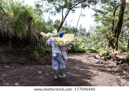 IJEN VOLCANO, INDONESIA - FEB 15:Worker carries sulfur inside crater on February 15, 2014 in Ijen Volcano, Indonesia. He carries the load of around 70kg to the top of the crater and then 3km down.  - stock photo
