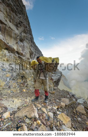 IJEN VOLCANO, INDONESIA - FEB 9: Worker carrying sulfur inside Ijen crater on Feb 9, 2014 in East Java, Indonesia. He carries the load of around 90kg to the top of the rip and then 3 km down. - stock photo