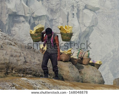 IJEN VOLCANO, INDONESIA - JAN 10:Worker carries sulfur inside crater on January 10, 2011 in Ijen Volcano, Indonesia. He carries the load of around 60kg to the top of the crater and then 3km down.  - stock photo