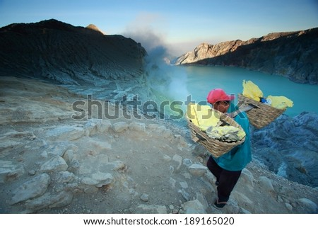 IJEN VOLCANO,INDONESIA - September 16: Workers are extracting sulphur inside Kawa Ijen crater on September 16, 2012 in East Java, Indonesia. People are working in really awful conditions.  - stock photo