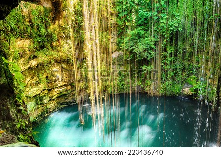 Ik-Kil Cenote near Chichen Itza, Mexico. Lovely cenote with transparent waters and hanging roots - stock photo
