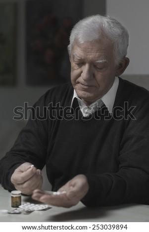 Ill and senior man taking pills, vertical  - stock photo