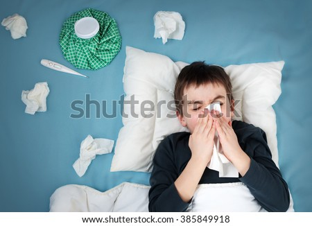 Ill boy lying in bed. sad child with fever and ice bag on head  - stock photo