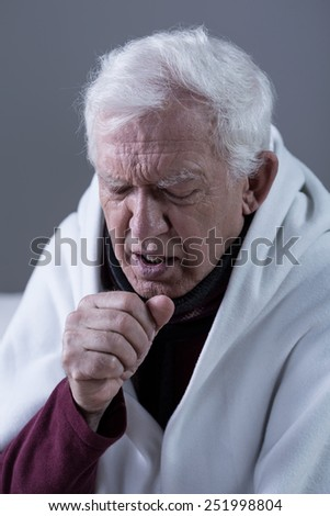 Ill coughing senior man covered with blanket - stock photo