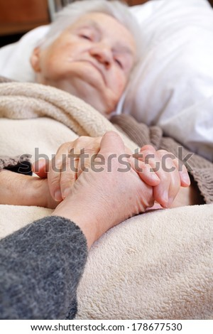 Ill elderly woman laying in the bed - stock photo