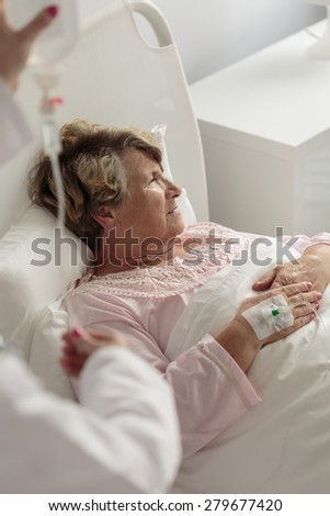 Ill female retiree being on a drip - stock photo