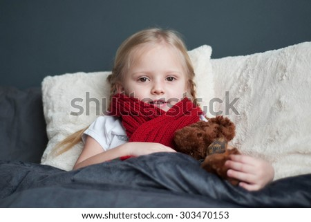 Ill girl with toy bear in the bed