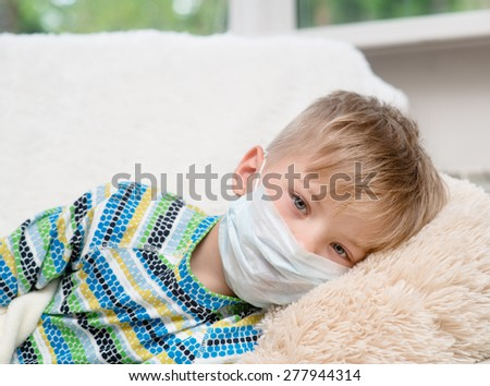 ill little boy in medicine health-care mask lying on bed - stock photo