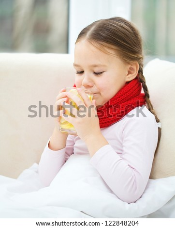 Ill little girl is drinking vitamin cocktail while sitting on a sofa - stock photo
