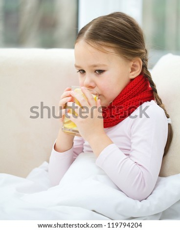 Ill little girl is grinning vitamin cocktail while sitting on a sofa - stock photo