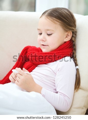 Ill little girl is reading thermometer while laying on sofa - stock photo