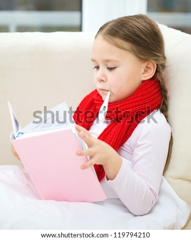 Ill little girl is sitting on sofa with thermometer in her mouth and reading book