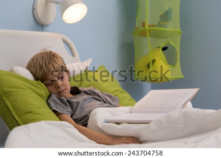 Ill little kid taking a nap during reading the book in his bed - stock photo