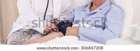 Ill man having measured blood pressure in hospital - stock photo
