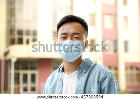 Ill man wearing mask on the street - stock photo