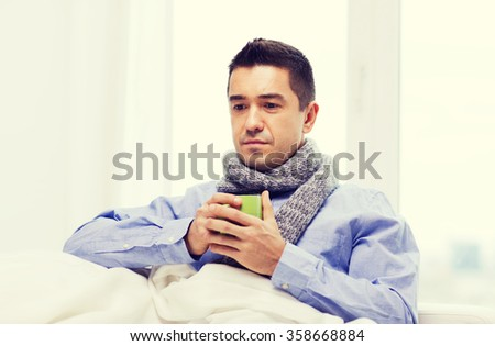 ill man with flu drinking hot tea from cup at home - stock photo
