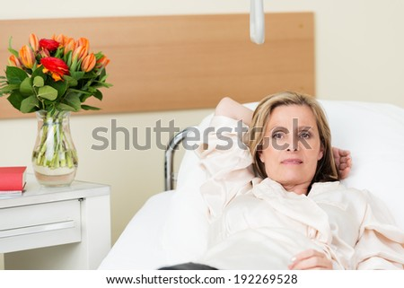 Ill middle-aged attractive blond woman lying in a hospital bed on a ward looking at the camera with a serious expression - stock photo
