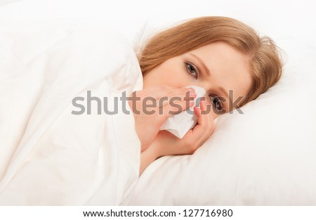 ill sick girl sneezes and blows her nose into a handkerchief in bed - stock photo