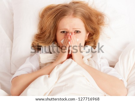 ill sick young woman sneezes and blows her nose into a handkerchief in bed - stock photo