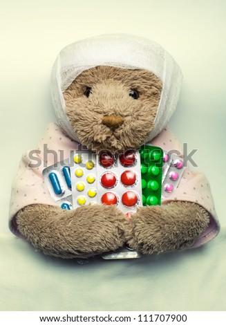 Ill teddy bear in bed with medicines - stock photo