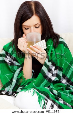 Ill woman covered with blanket drink tea, hold cup and pack of pills, sitting at home on sofa couch - stock photo