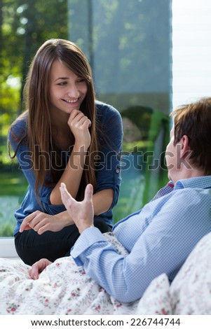 Ill woman lying in bed talking with her granddaughter - stock photo