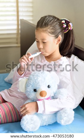 Ill young Asian girl with black hair, sitting on bed with a thermometer, measuring the height of her fever and hugs the blue teddy bear.