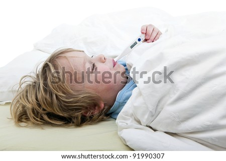 Ill young child, lying in bed with a thermometer, measuring the height of his fever - stock photo