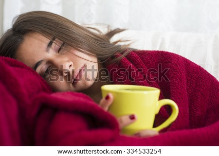 ill young girl with fever drinking cup of warm tea - stock photo