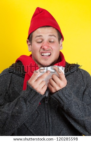 Ill young man with red nose, scarf and cap sneezing into handkerchief - stock photo