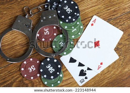 Illegal gambling concept blackjack with betting chips and handcuffs - stock photo