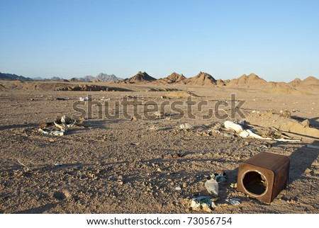 Illegal waste dump in the desert, mountains in the background against a blue sky. South Sinai, Egypt.