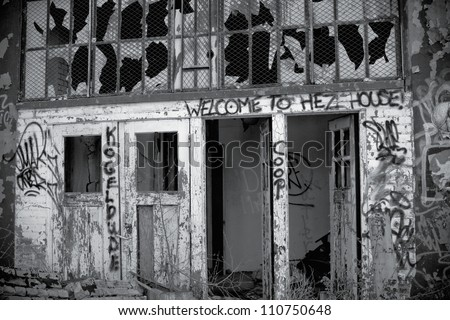 Illegally painted graffiti in an abandoned building in Detroit, Michigan. The Windows are broken out and piles of bricks and old tires are scattered about. - stock photo