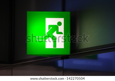 Illminated green exit sign attached to a wall in a public transportation facility. Signage consists of a human figure running and exiting through a door opening. - stock photo