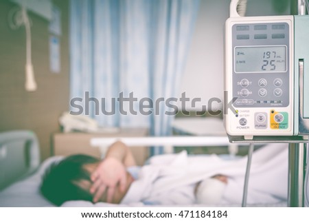 Illness asian boy lying on sickbed in hospital with infusion pump intravenous IV drip. Shallow depth of field, IV machine in focus. Health care and medical concept. Vintage tone effect.