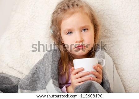 Illness child. Little girl wrapped in a blanket with mug - stock photo