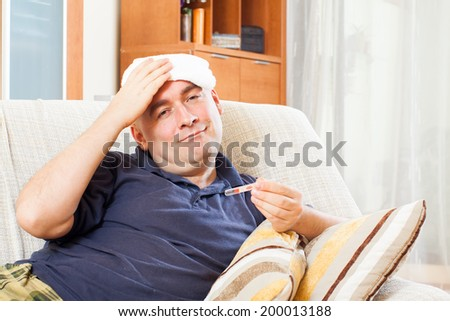Illness  man with thermometer stupes  towel to  head at home