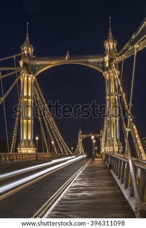Illuminated Albert bridge in west London at night - stock photo