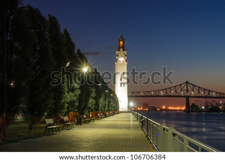 Illuminated Alley, and in the background .. the Clock of Old Montreal and part of the Jacques Cartier Bridge. - stock photo