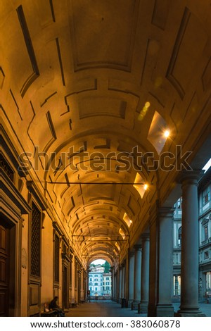 Illuminated and patterned barrel vault behind row of doric columns