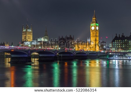 Illuminated Big Ben with bridge and reflection on the river in the foreground at night London United Kingdom.  Clock tower.