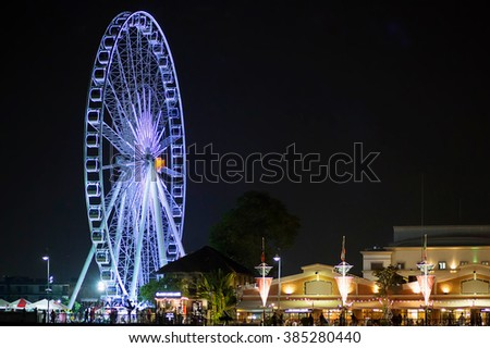 Illuminated big wheel in night Bangkok, Phuket. Image with selective focus and toning