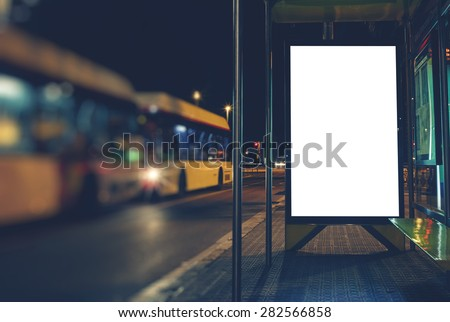 Illuminated blank billboard with copy space for your text message or content, advertising mock up banner of bus station, public information board in night city, auto bus stop empty poster - stock photo