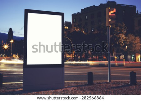 Illuminated blank billboard with copy space for your text message or content, public information board in night city with beautiful dusk on background, advertising mock up banner in metropolitan city - stock photo