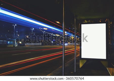 Illuminated blank billboard with copy space for your text message or promotional content, advertising mock up banner on bus stop in night, public information board with blurred vehicles on high speed - stock photo