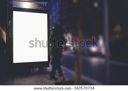 Illuminated blank billboard with copy space for your text message or promotional content, public information board on the bus stop, empty advertising mock up banner in metropolitan city in evening  - stock photo