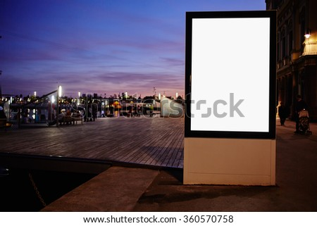 Illuminated blank billboard with copy space for your text message or promotional content,public information board against sunset sky,mock up in urban setting at night,empty banner in metropolitan city - stock photo