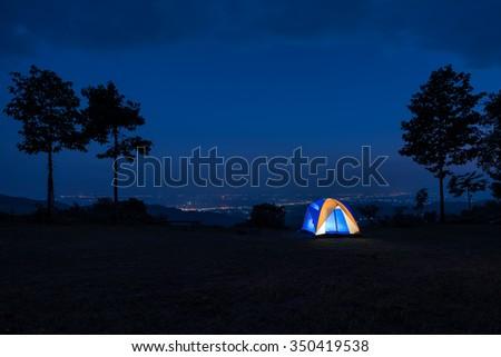 Illuminated Blue Camping tent at Night - stock photo